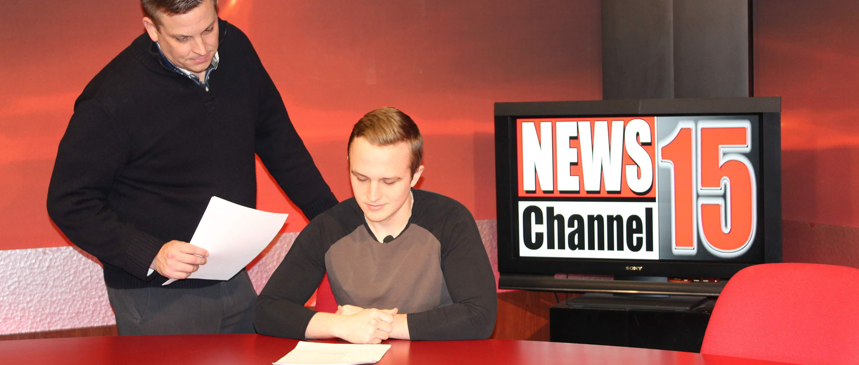 WVC Broadcasting Director Kyle peach coaches one of his students before a broadcast.