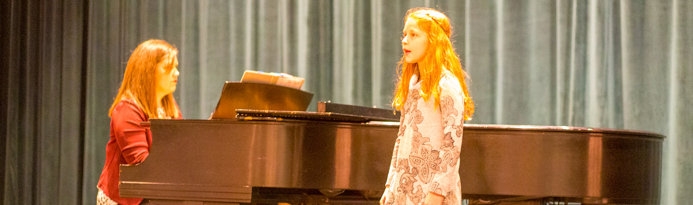 Child singing with pianist accompanying her