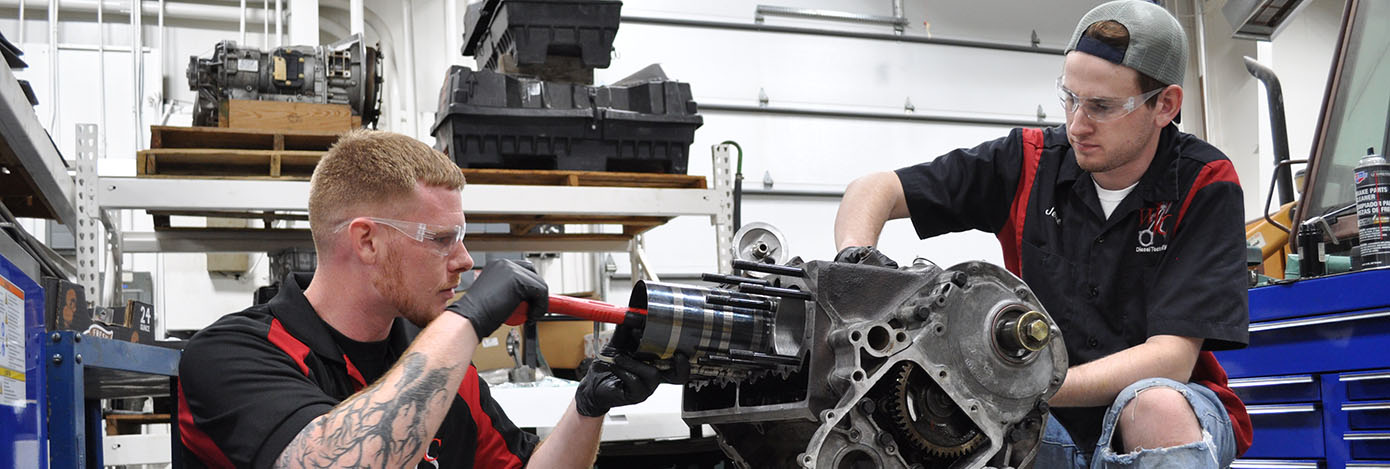 Two diesel tech students work on an engine project.