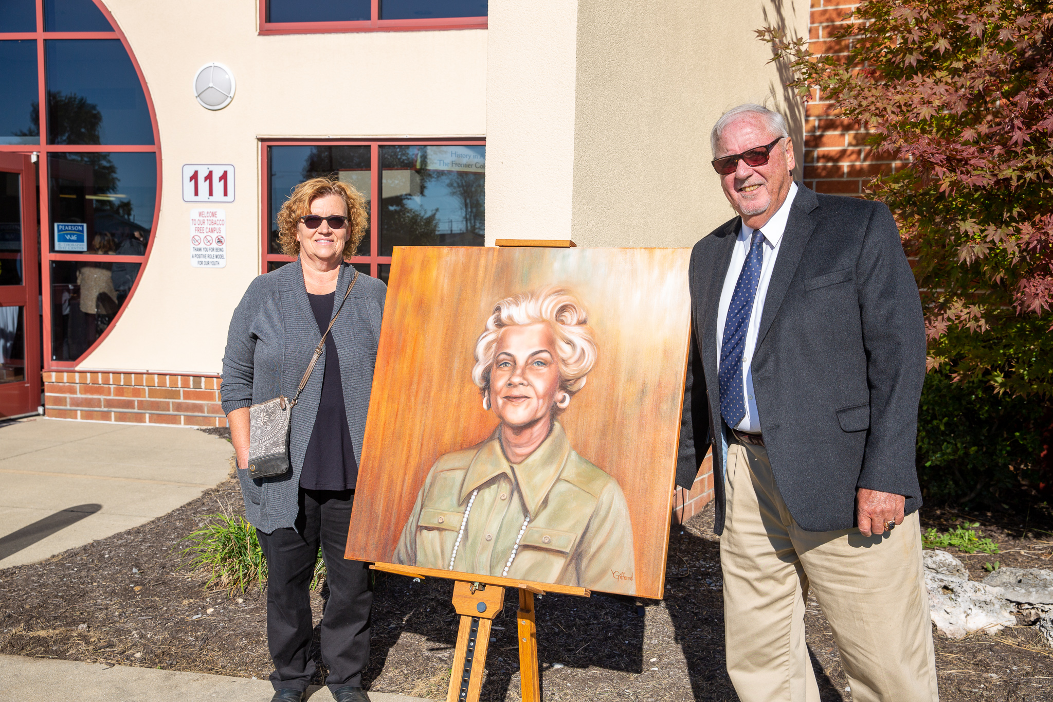 Vicki Gifford poses with painting of Jerry Cox's mother
