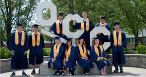 Grads standing in front of OCC Statue